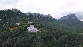 Vista aerea del metraggio del fuco: Volo sopra le montagne nuvolose con le foreste Pic Saint Loup, Hortu video d archivio