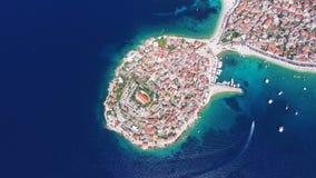 Vista aerea del motoscafo che passa la penisola di Primosten, Croazia stock footage
