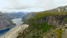 Vista aerea del paesaggio della Norvegia Il tipo e la ragazza stanno stando sull'orlo di una roccia enorme norway Trolltunga archivi video