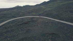 Vista aerea del pendio dell'Etna Fuco volante sopra la strada su cui l'automobile sta viaggiando L'Italia, Sicilia video d archivio