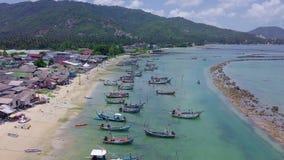 Vista aerea del pescatore Village con molti pescherecci tradizionali messi in bacino dalla riva di mare in Tailandia video d archivio