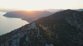 Vista aerea del tramonto sopra bei Mar Nero e montagne su un fondo del cielo di tramonto archivi video