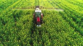 Vista aerea del trattore agricolo che ara e che spruzza sul campo archivi video