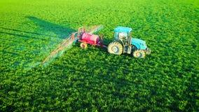 Vista aerea del trattore agricolo che ara e che spruzza sul campo video d archivio