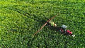 Vista aerea del trattore agricolo che ara e che spruzza sul campo stock footage
