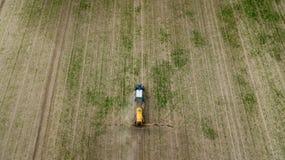 Vista aerea del trattore agricolo che ara e che spruzza sul campo fotografie stock libere da diritti
