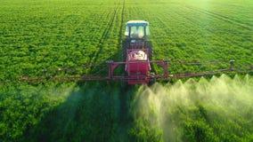 Vista aerea del trattore agricolo che ara e che spruzza sul campo verde stock footage