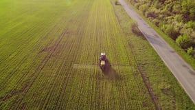 Vista aerea del trattore agricolo che spruzza sul campo con lo spruzzatore, i diserbanti e gli antiparassitari al tramonto Attrez archivi video