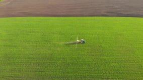 Vista aerea del trattore agricolo che spruzza sul campo con lo spruzzatore, i diserbanti e gli antiparassitari al tramonto Attrez video d archivio