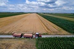 Vista aerea del trattore con i rimorchi sulla strada rurale Fotografia Stock