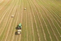 Vista aerea del trattore con la pressa per balle rotonda sul campo Fotografia Stock Libera da Diritti