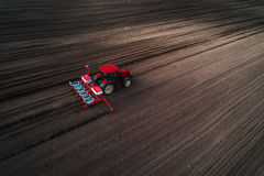 Vista aerea del trattore rosso che prepara campo con il cultivaror del seedbad Agricoltore che semina terra Immagini Stock Libere da Diritti
