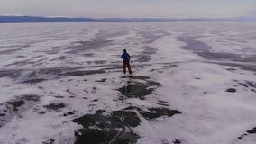 Vista aerea del viaggiatore che pattina sul ghiaccio di un lago congelato archivi video