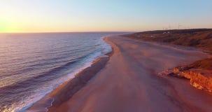 Vista aerea dell'oceano, del faro del nord al tramonto, Portogallo di Nazare e della spiaggia archivi video