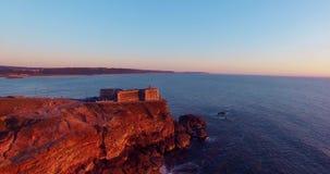 Vista aerea dell'oceano e del faro al tramonto, Portogallo di Nazare video d archivio