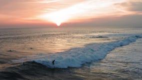 Vista aerea dell'onda di oceano di tramonto di guida del surfista Il fuco 4k ha sparato lo stile di vita praticante il surfing de archivi video