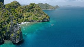 Vista aerea della barca di luppolizzazione di isola turistica che lascia la spiaggia di Entalula con acqua cristallina e la bella stock footage