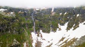 Vista aerea della cascata alta nelle montagne alpine Fotografie Stock Libere da Diritti