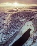 Vista aerea della città suburbana accanto ad un fiume e dei campi al tramonto nell'inverno Fotografia Stock Libera da Diritti