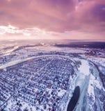Vista aerea della città suburbana accanto ad un fiume e dei campi al tramonto nell'inverno Fotografia Stock