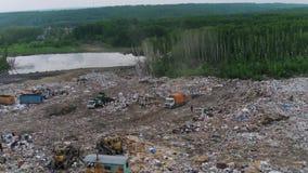 Vista aerea della discarica enorme della città al tramonto Il camion di immondizia scarica i rifiuti video d archivio