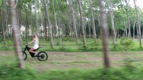 Vista aerea della donna sulla bicicletta elettrica nella foresta archivi video
