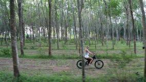 Vista aerea della donna sulla bicicletta elettrica nella foresta stock footage