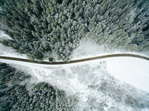 Vista aerea della foresta nevosa con una strada Fotografia Stock