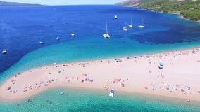 Vista aerea della gente che prende il sole su una spiaggia sabbiosa sull'isola di Brac, Croazia archivi video
