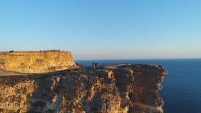Vista aerea della gente che sta su una grande scogliera contro il chiaro cielo blu e l'acqua di mare blu colpo Bella vista da fotografia stock libera da diritti