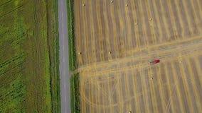 Vista aerea della lavorazione del fieno trasformata in balde rotonde Il trattore rosso funziona sul campo Sul lato del campo è video d archivio