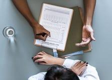 Vista aerea della lista di controllo paziente di rapporto quotidiano di scrittura di medico immagini stock