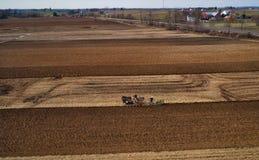 Vista aerea della manodopera agricola di Amish che gira il campo in primavera in anticipo come visto in fuco immagine stock libera da diritti
