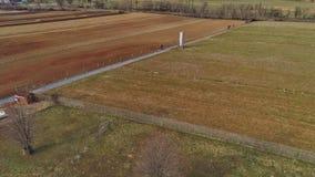 Vista aerea della manodopera agricola di Amish che gira il campo in primavera in anticipo come visto in fuco fotografia stock