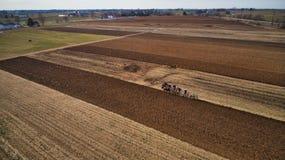 Vista aerea della manodopera agricola di Amish che gira il campo in primavera in anticipo come visto in fuco fotografia stock libera da diritti
