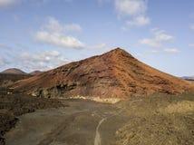 Vista aerea della montagna di Bermeja di un colore rosso intenso, circondata dai giacimenti di lava, Lanzarote, isole Canarie, Sp immagine stock libera da diritti