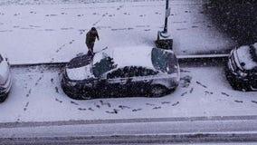 Vista aerea della neve e del ghiaccio di pulizia dell'uomo fuori dalla sua finestra dello schermo di vento dell'automobile stock footage