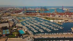 Vista aerea della porta commerciale e del porticciolo con gli yacht a Valencia Terminale e nave di contenitore durante il caricam archivi video
