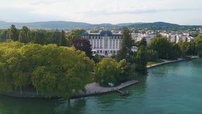 Vista aerea della residenza bianca e blu di lusso vicino alle alte montagne verdi del waterwith e del parco sui precedenti archivi video