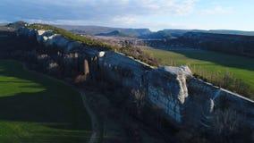 Vista aerea della scogliera massima e lunga di pietra naturale sbalorditiva della parete, con gli alberi crescenti ed i campi ver fotografia stock