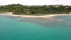Vista aerea della spiaggia sbalorditiva sotto un villaggio turistico, Athitos Halkidiki Grecia, movimento di andata del turchese  video d archivio