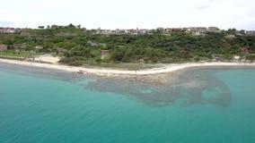 Vista aerea della spiaggia sbalorditiva sotto un villaggio turistico, Athitos Halkidiki Grecia, movimento a rovescio del turchese video d archivio