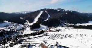Vista aerea della stazione sciistica in montagne carpatiche all'inverno archivi video