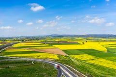 Vista aerea della strada che passa attraverso un paesaggio rurale con fioritura Fotografie Stock