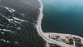 Vista aerea della strada nella foresta e nel lago di inverno fotografie stock libere da diritti