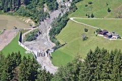 Vista aerea della torrente montano nelle alpi austriache bloccate dopo una colata di fango massiccia con funzionamento del camion Fotografia Stock