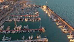 Vista aerea delle barche nel porto, con le costruzioni della città dietro stock footage