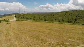 Vista aerea delle colline stupefacenti coperte in alberi ed in cespugli verdi, grande parco eolico video d archivio