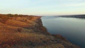 Vista aerea delle colline sulla riva del fiume al tramonto stock footage