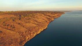 Vista aerea delle colline sulla riva del fiume al tramonto archivi video